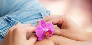 una flor encima de la barriga de una mujer como símbolo a la fertilidad